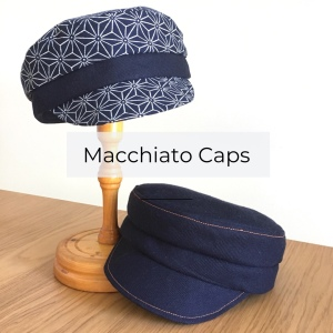 A photograph of two dark blue Macchiato Caps on a pale wooden table